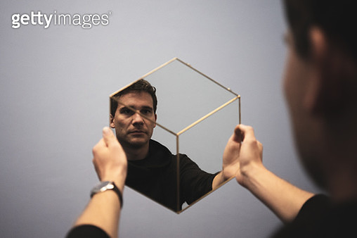 Man Holding Mirror With Reflection Against White Wall - gettyimageskorea