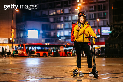 Delivery woman with electric scooter checking address on phone - gettyimageskorea