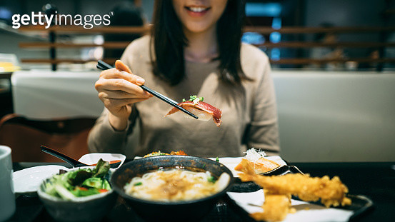 Joyful young woman enjoying sushi, seafood tempura, soup udon, salad and green tea in a Japanese restaurant - gettyimageskorea