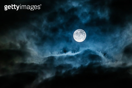 Bright full moon glowing in a cloudy sky - gettyimageskorea