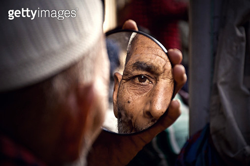 Close-Up Of Man Holding Mirror With Reflection - gettyimageskorea