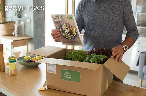 Men received box loaded with organic vegetables from delivery service. He is up to make some fantastic vegan meal. Reading food recipe that came in the box - gettyimageskorea