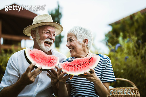 Cheerful mature couple having fun while eating watermelon during picnic day in nature. - gettyimageskorea