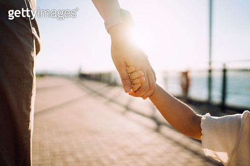 Close up of young Asian mother walking hand in hand with her little daughter enjoying family bonding time in a park along the promenade at sunset - gettyimageskorea