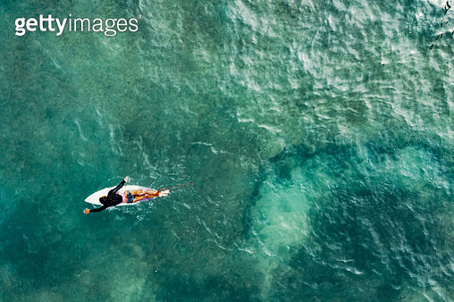 Directly above of a mature woman on a surfboard paddling out to the waves while surfing in a tropical setting - gettyimageskorea
