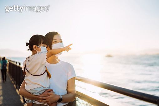 Daily life of a young Asian mother and cute little daughter with protective face mask, enjoying family bonding time in a park by the promenade looking at view at sunset - gettyimageskorea