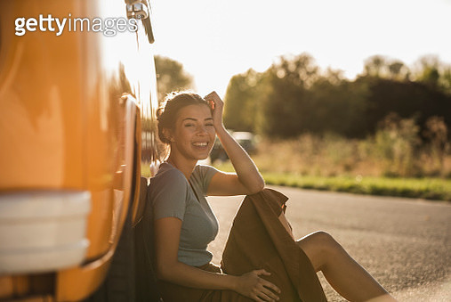 Pretty woman on a road trip with her camper, relaxing at the roadside - gettyimageskorea