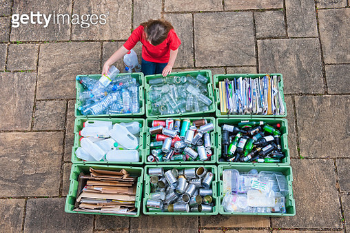 Caucasian teenage girl organizing recycling bins - gettyimageskorea
