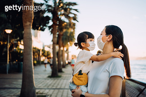 Young Asian mother with cute little daughter in protective face mask enjoying family bonding time embracing and chatting joyfully while having a walk along the promenade in the park at sunset - gettyimageskorea