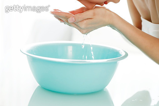 Young woman bent over bowl, washing face - gettyimageskorea