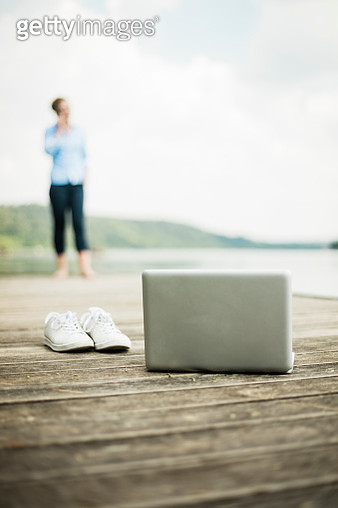 Laptop and shoes on jetty at a lake with woman in background - gettyimageskorea