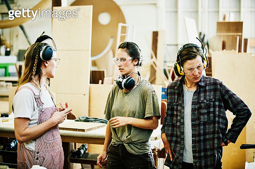 Female woodworkers discussing cabinet project in woodshop - gettyimageskorea