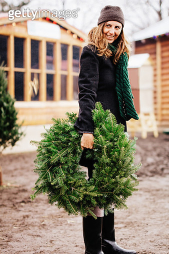 Woman holding a Christmas wreath - gettyimageskorea