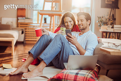 Close up of a young couple having coffee and using a phone in the morning - gettyimageskorea