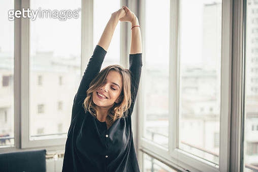 Woman stretching and doing exercises in the morning at her apartment - gettyimageskorea