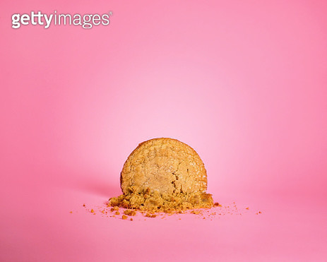 Large smashed homemade vegan, gluten free peanut butter cookie on a pink background. - gettyimageskorea