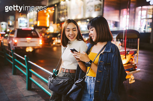 Vintage toned image of two young, Asian women, walking together, chatting, near Siam station on Bangkok Sukhumvit line. They're wearing casual street style clothing, enjoying an afternoon together, texting on their cellphones. - gettyimageskorea