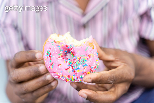 Young man eating donut - gettyimageskorea