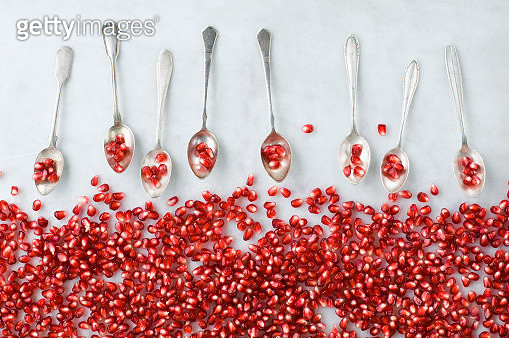 Pomegranate seeds and row of silver tea spoons on white marble - gettyimageskorea