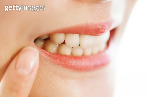 Young woman pointing at teeth - gettyimageskorea