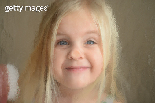 Young girl smiles through distorted glass - gettyimageskorea