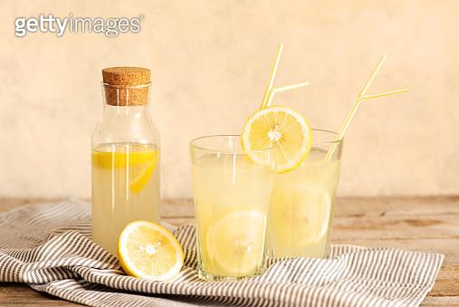 Jar of tasty fresh lemonade with lemons in background - gettyimageskorea