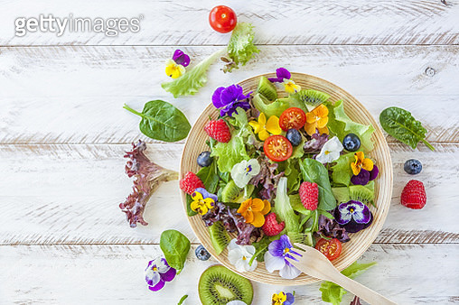 Purple and green lettuce, pansies and violets edible flowers, fork of wood and bamboo plate on wooden table. - gettyimageskorea