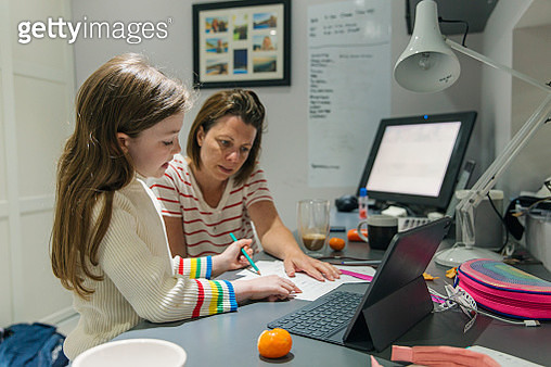 Woman helping daughter with her home schooling - gettyimageskorea