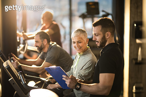 Happy senior woman and her coach reading training plan on a spinning class in a gym. - gettyimageskorea