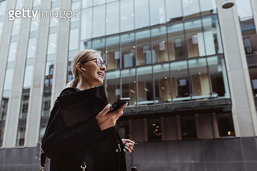 Low angle view of businesswoman talking through in-ear headphones in city - gettyimageskorea