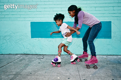Black mother holding waist of daughter wearing roller skates - gettyimageskorea