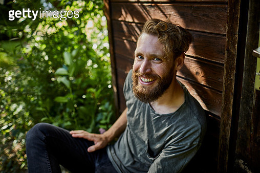 Portrait of smiling bearded man resting at garden shed - gettyimageskorea