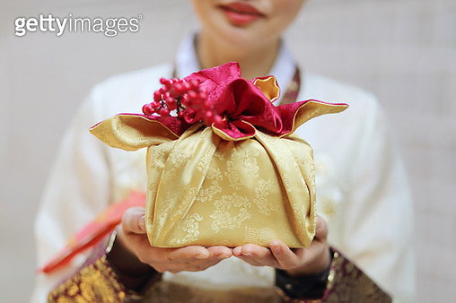 Woman wearing Korean traditional clothes with gift box - gettyimageskorea
