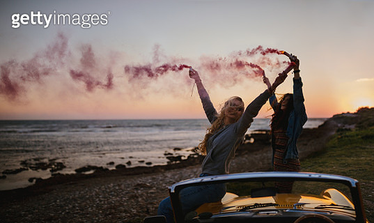 Hipster women having fun with smoke bombs at beach - gettyimageskorea