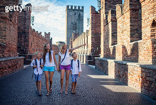 Family sightseeing beautiful Italian town of Verona. Mother and three kids are walking on Ponte Scaligero bridge towards the old town centre.Sunny summer day in Verona, Veneto, Italy.Nikon D850 - gettyimageskorea
