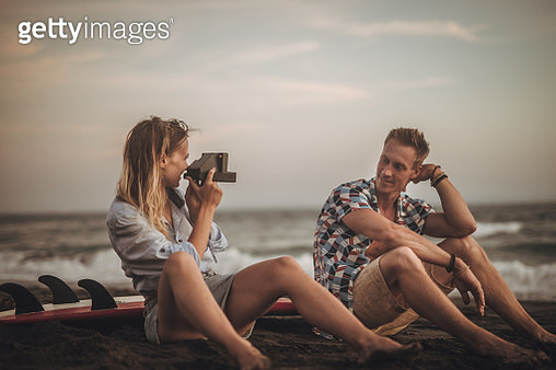Two people, man and woman on the beach by the sea, girlfriend taking pictures of her boyfriend with instant by the sea. - gettyimageskorea