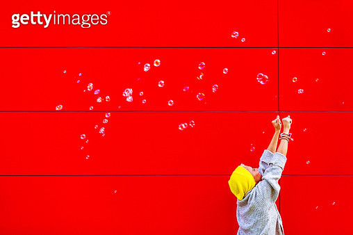 Young woman chasing bubbles against the red wall - gettyimageskorea