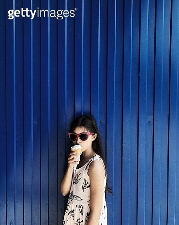 Portrait Of Girl Eating Ice Cream While Standing Against Blue Corrugated Iron - gettyimageskorea