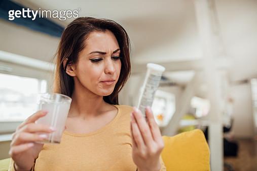 Woman taking effervescent tablet - gettyimageskorea