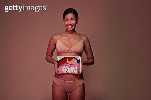Young woman holding tablet in front of stomach to look inside the body - gettyimageskorea
