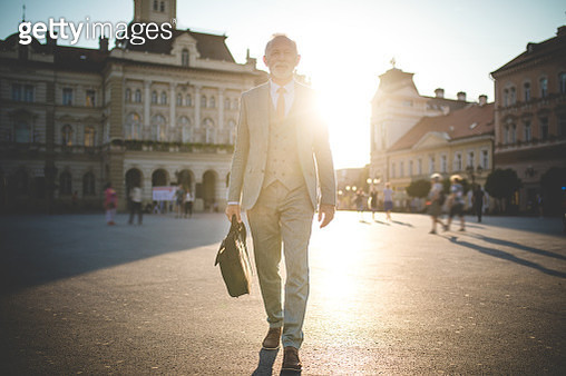 Confident senior man going to work on a sunny day - gettyimageskorea