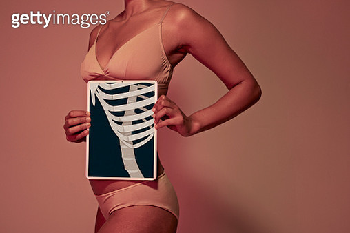 Young woman holding tablet in front of body to show rib bones - gettyimageskorea