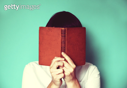 Woman's holding a book in front of her face - gettyimageskorea