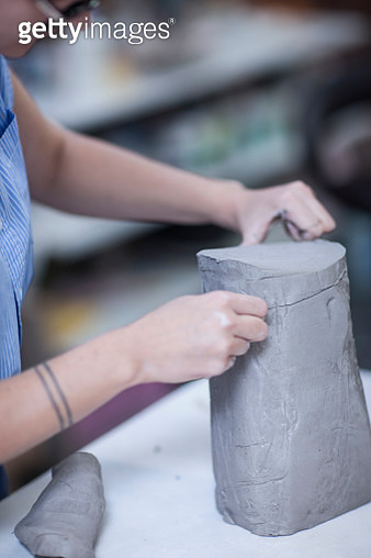Cropped shot of female potters slicing clay in workshop - gettyimageskorea
