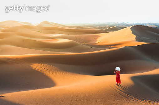 High angle view of an elegant woman with straw hat enjoying the sunset from the top of a sand dune. - gettyimageskorea