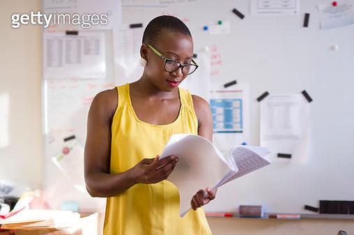 Woman reading in an office - gettyimageskorea
