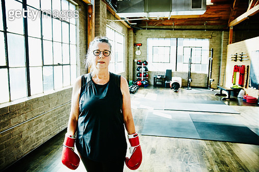 Senior woman in gym wearing boxing gloves - gettyimageskorea