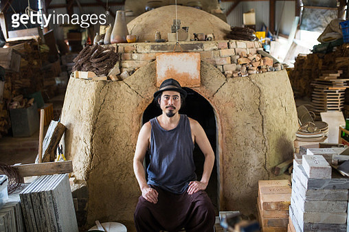 A portrait of a potter in front of his homemade wood-fired kiln - gettyimageskorea