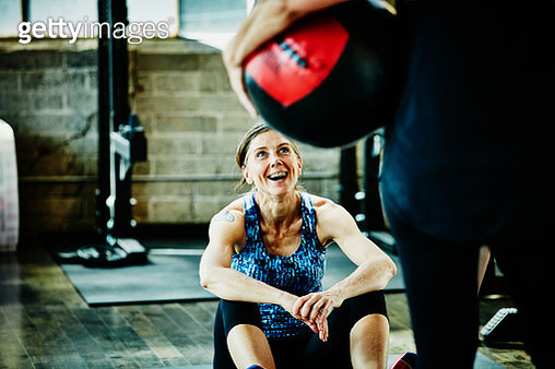 Laughing mature woman doing medicine ball crunches - gettyimageskorea