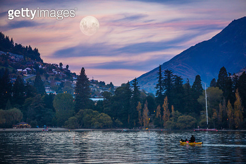 Sunset descends over Queenstown's Lake Wakatipu. A man kayak's under a full moon. - gettyimageskorea